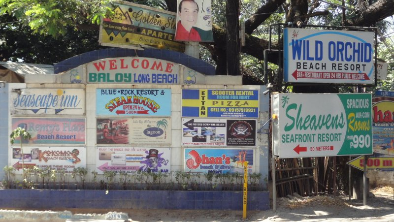 The signs at the entrance to Baloy Beach Road by National Highway